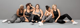 Five women sit in a row on a gray floor modeling styles in black, white and gray